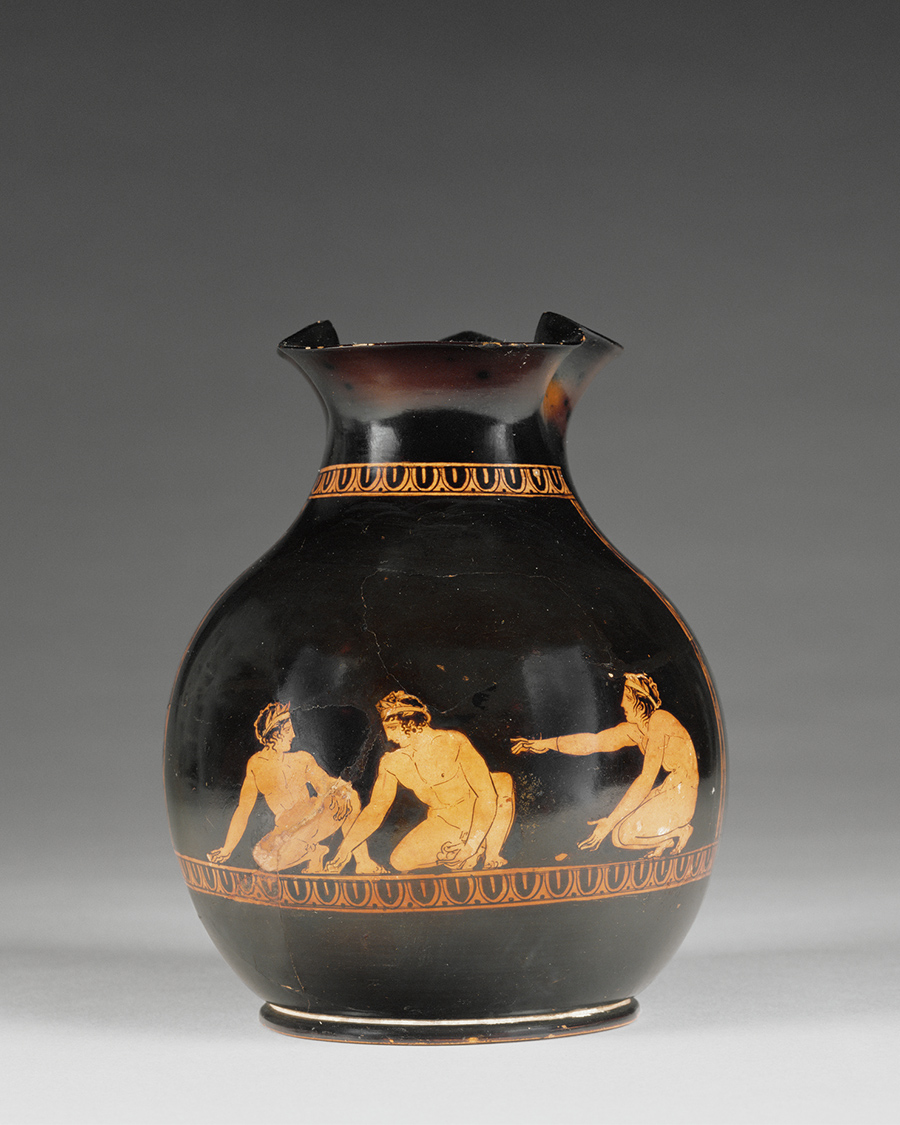 A black vase with a fluted lip is decorated with three nude men wearing crowns of leaves and squatting to play a game of knucklebones.