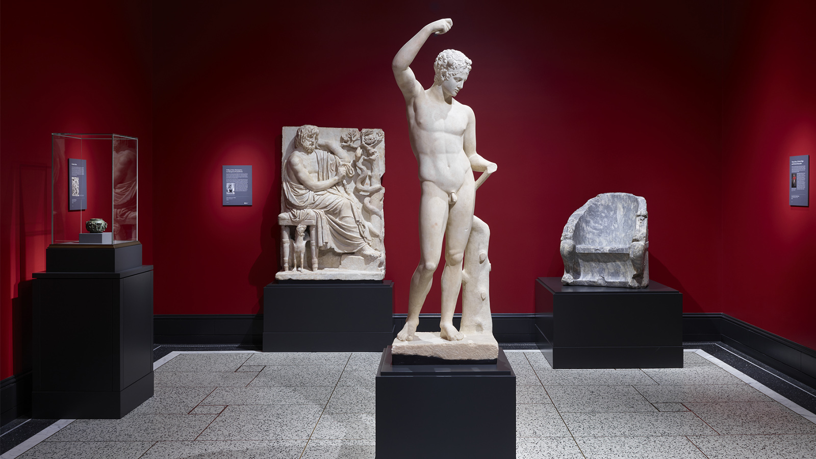 A vitrine holding a small work of art and three large marble sculptures, including a throne, satyr, and relief dominate a small room with dramatic red walls.