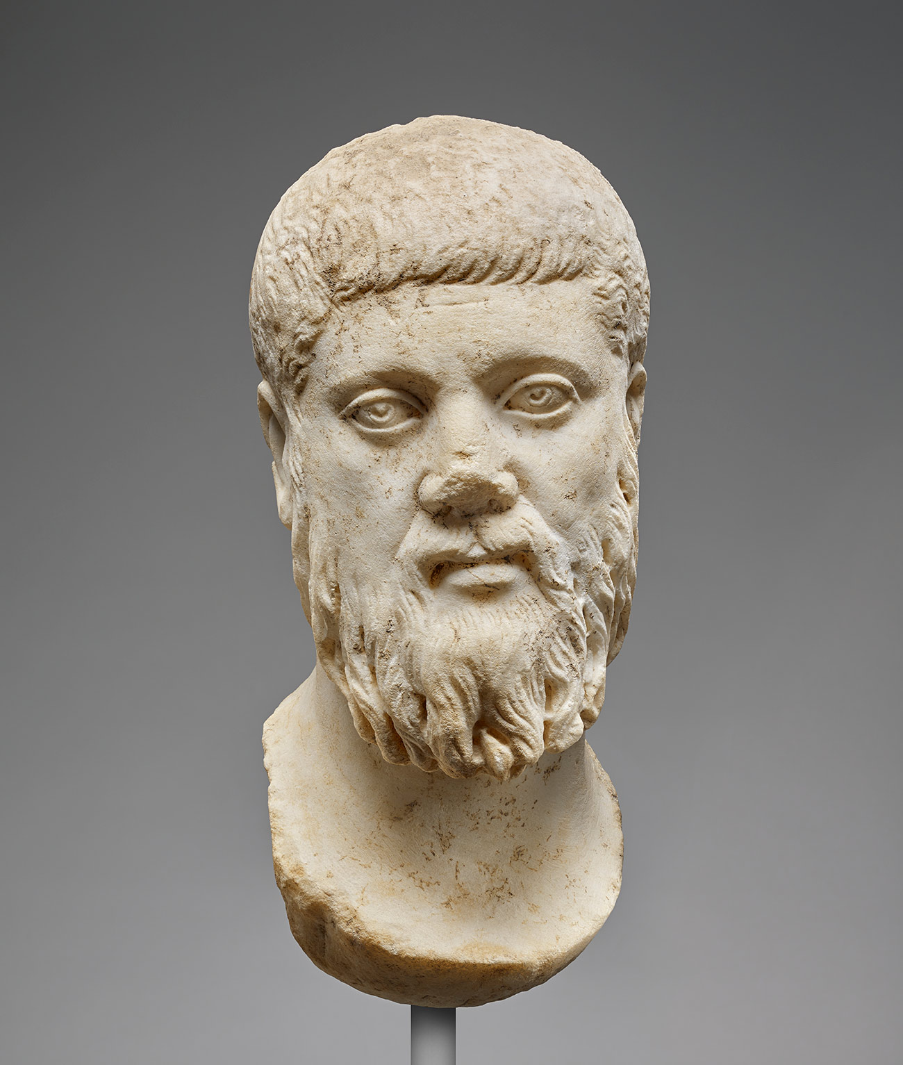 Marble head of a bearded, pensive philosopher, his head slightly turned, making eye contact with the viewer