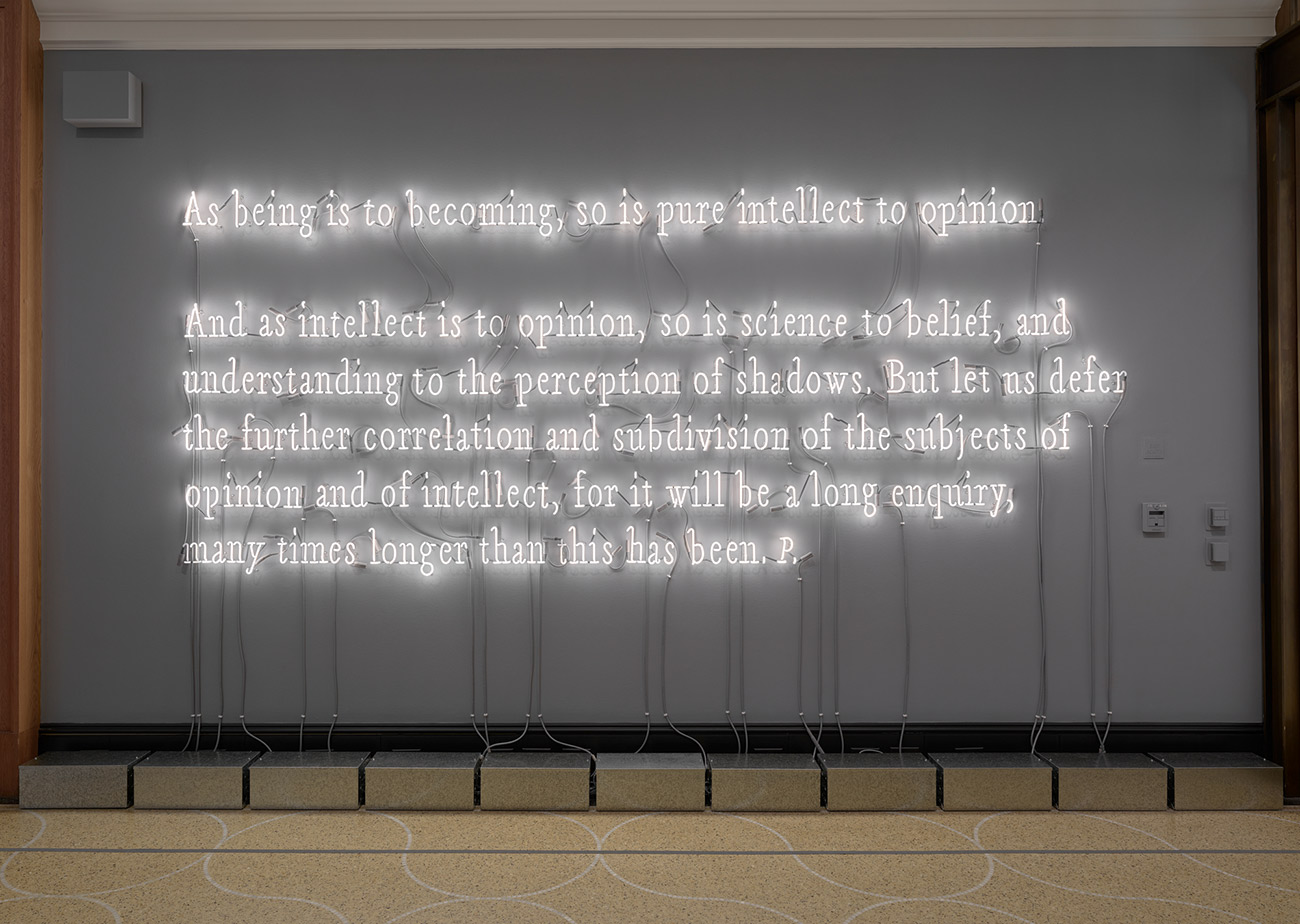 A dark grey wall with handwriting of a Platonic text sculpted in neon tubing