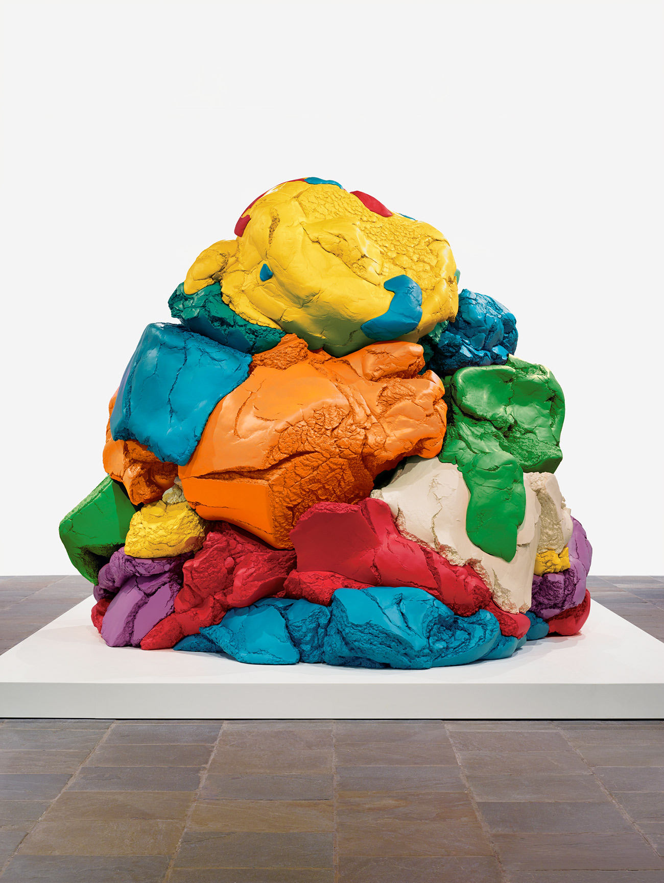 A large, colorful sculpture is crafted to exactly resemble a heap of children's play-doh, but at a massive scale