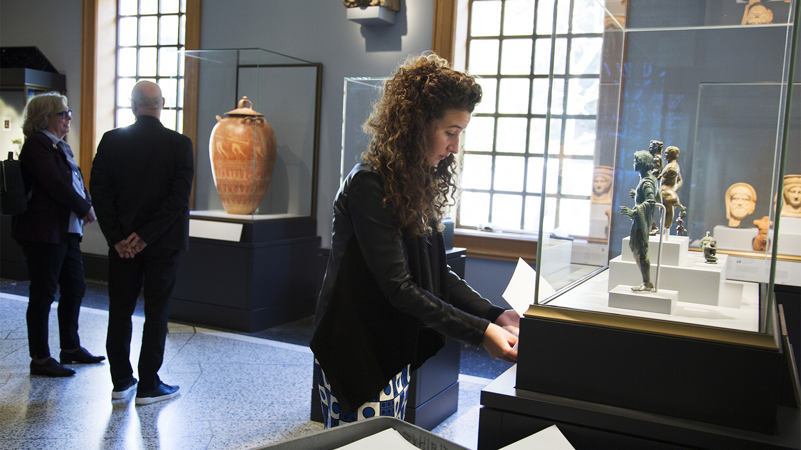 A young woman with long curly hair and wearing a leather jacket places a white label on the pedestal of a case above which are about five small bronze statuettes.
