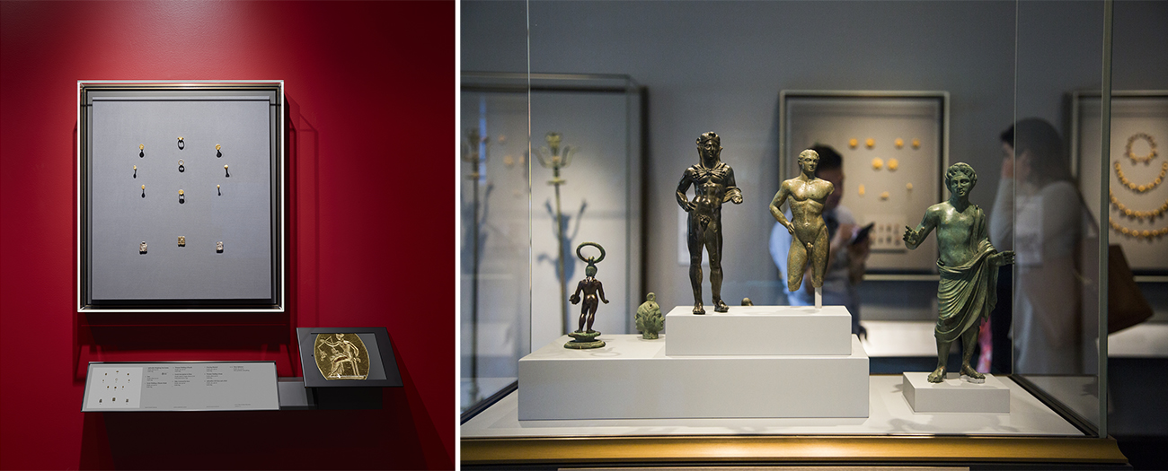 Left: Framed by the deep red wall on which it hangs, a shallow rectangular case holds small gold artifacts against a gray background. Below is a plaque with information about the artifacts and to its right is an iPad displaying a close-up of one of the artifacts. Right: Four small bronze statuettes of male figures and one depicting a two-faced head are displayed in a shallow vitrine.