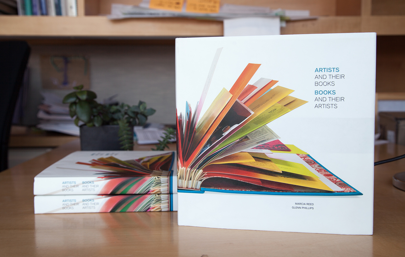 A stack of copies of the book Artists and Their Books sitting on a desk
