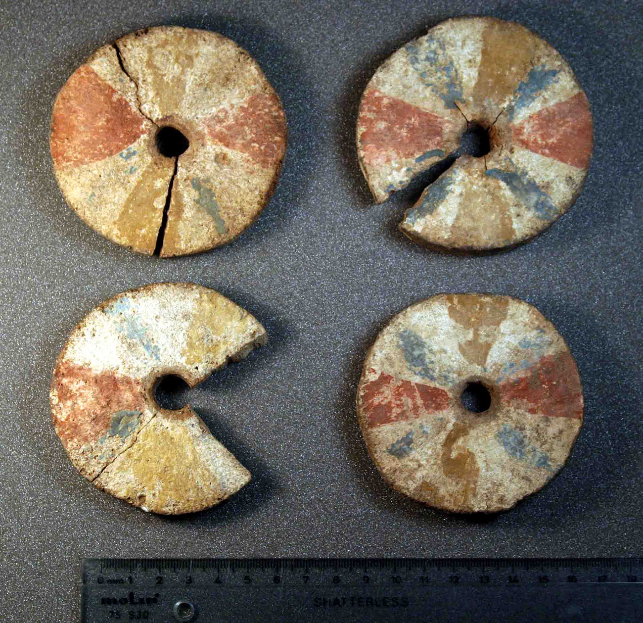 Four brightly painted wooden disks with holes in the center. Three are cracked or missing pieces.