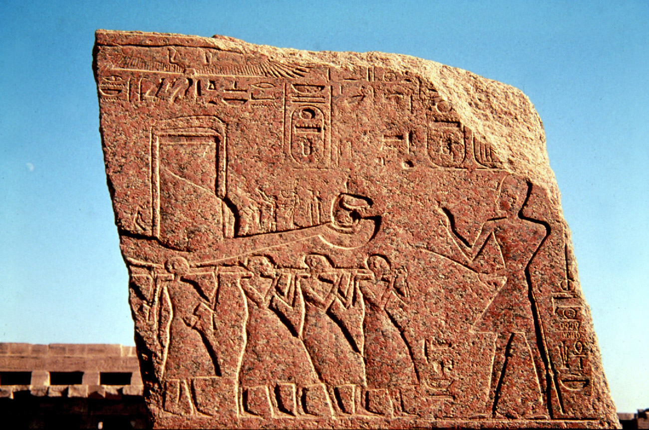 A relief carved in stone showing Egyptian style figures carrying a boat with hieroglyphics above.