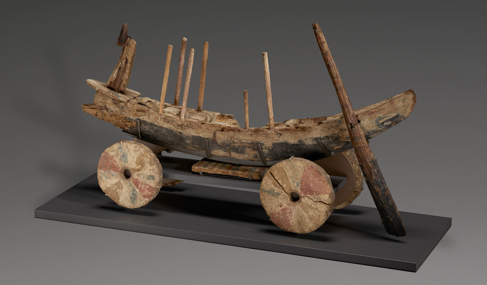 A worn and weathered wooden boat model with bright but faded paint. The boat has four wheels below, some rods jut up from the center and a rudder hangs down.