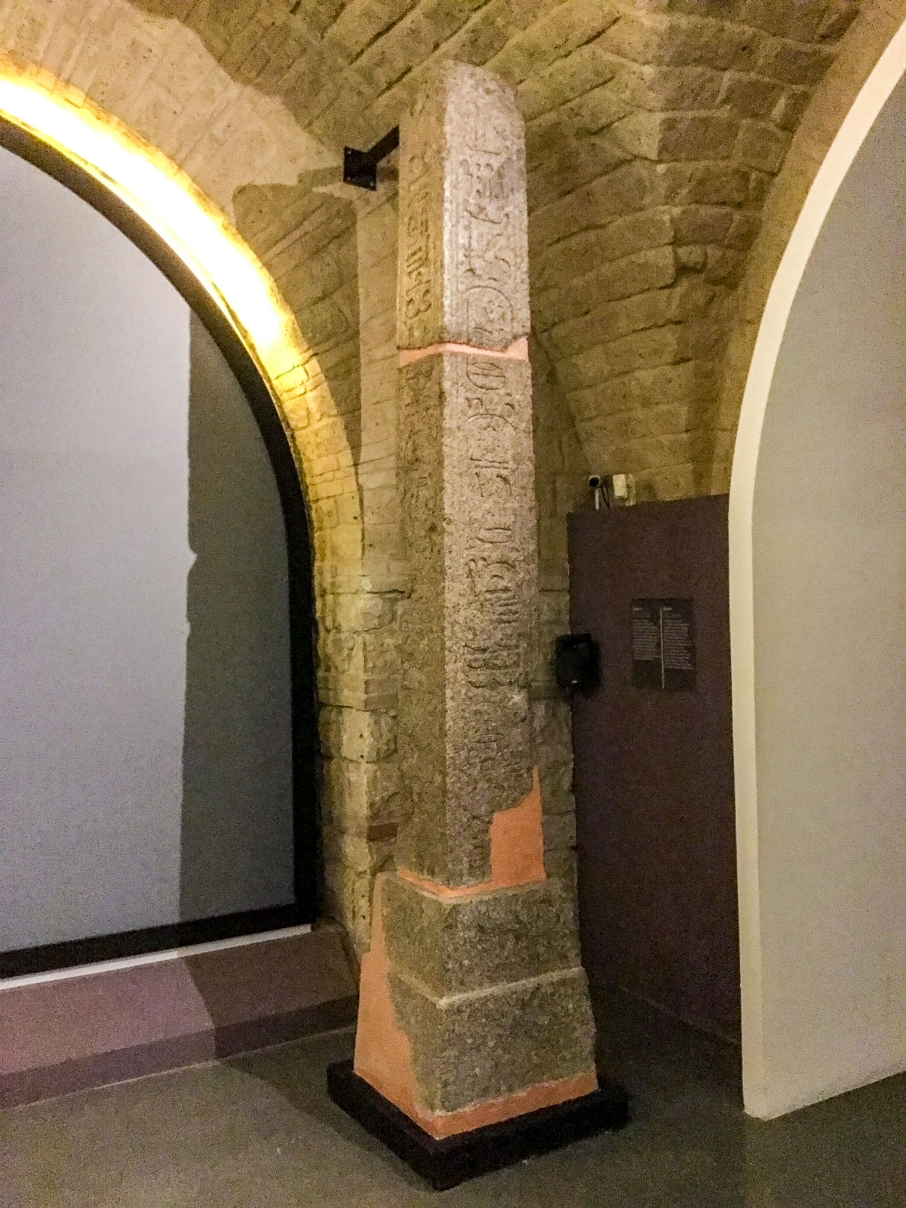 The same stone obelisk shown above but in a darker room, with orange repair patches and a metal arm connected to a stone wall supporting it.