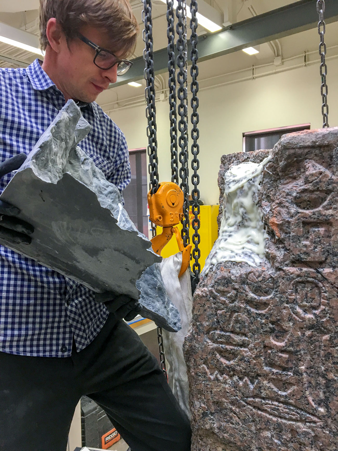 A man with gloves holds a large gray piece that appears to fit into a damaged section of a block of stone carved with hieroglyphics.
