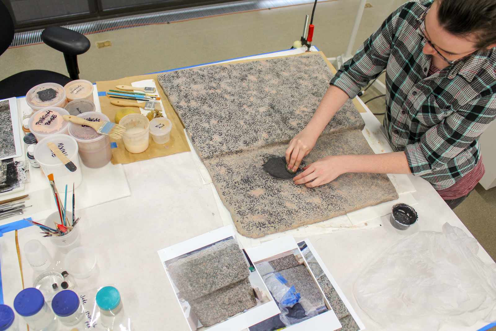 A woman at a table with photos of granite blocks blots a panel to create a textured look.