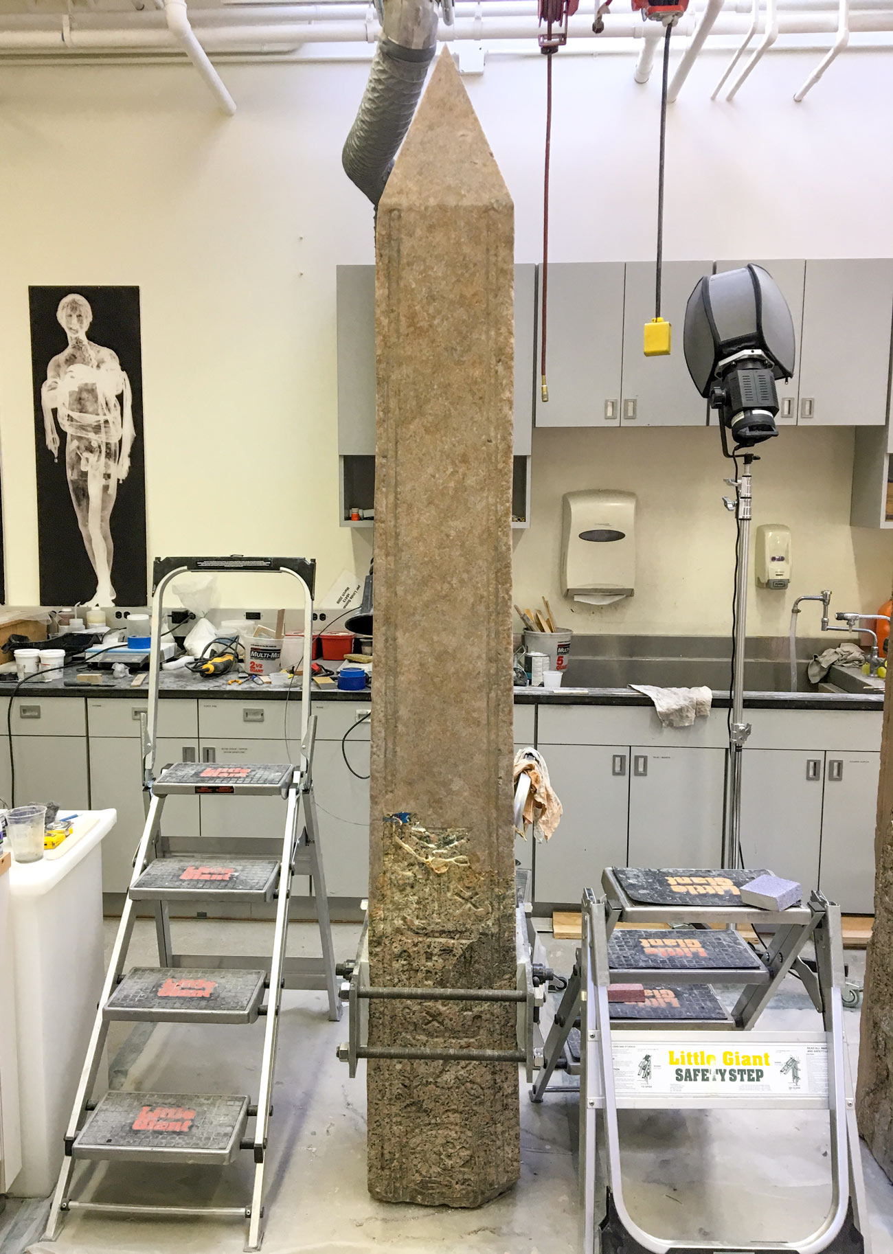 The obelisk in the lab surrounded by step-stools and equipment, painted.