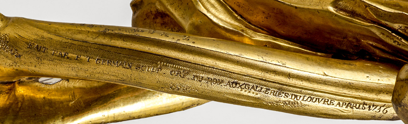 A detail of a gold twisting vine with lettering reading in part galleries du Louvre