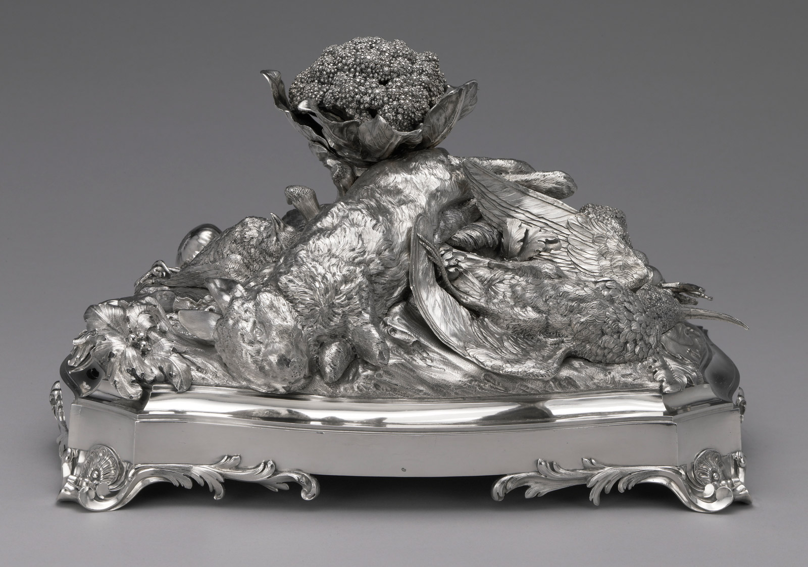 A silver centerpiece consisting of a still life of a rabbit, a bird, and leafy vegetables and a head of cauliflower.