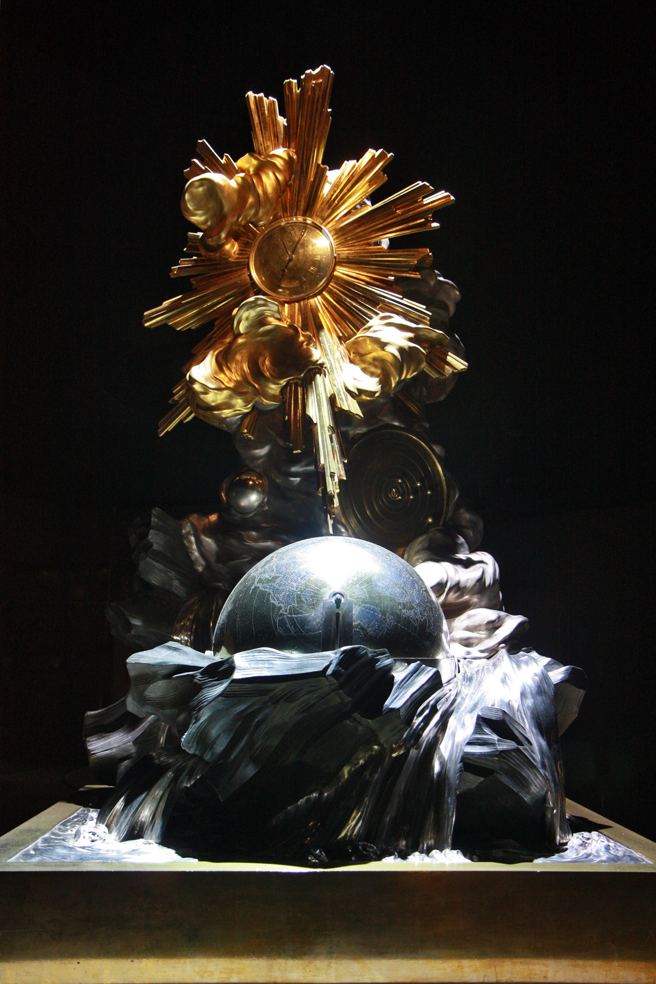 A decorative clock consisting of a dark sphere below and a clock surrounded by a brilliant gold sunburst.