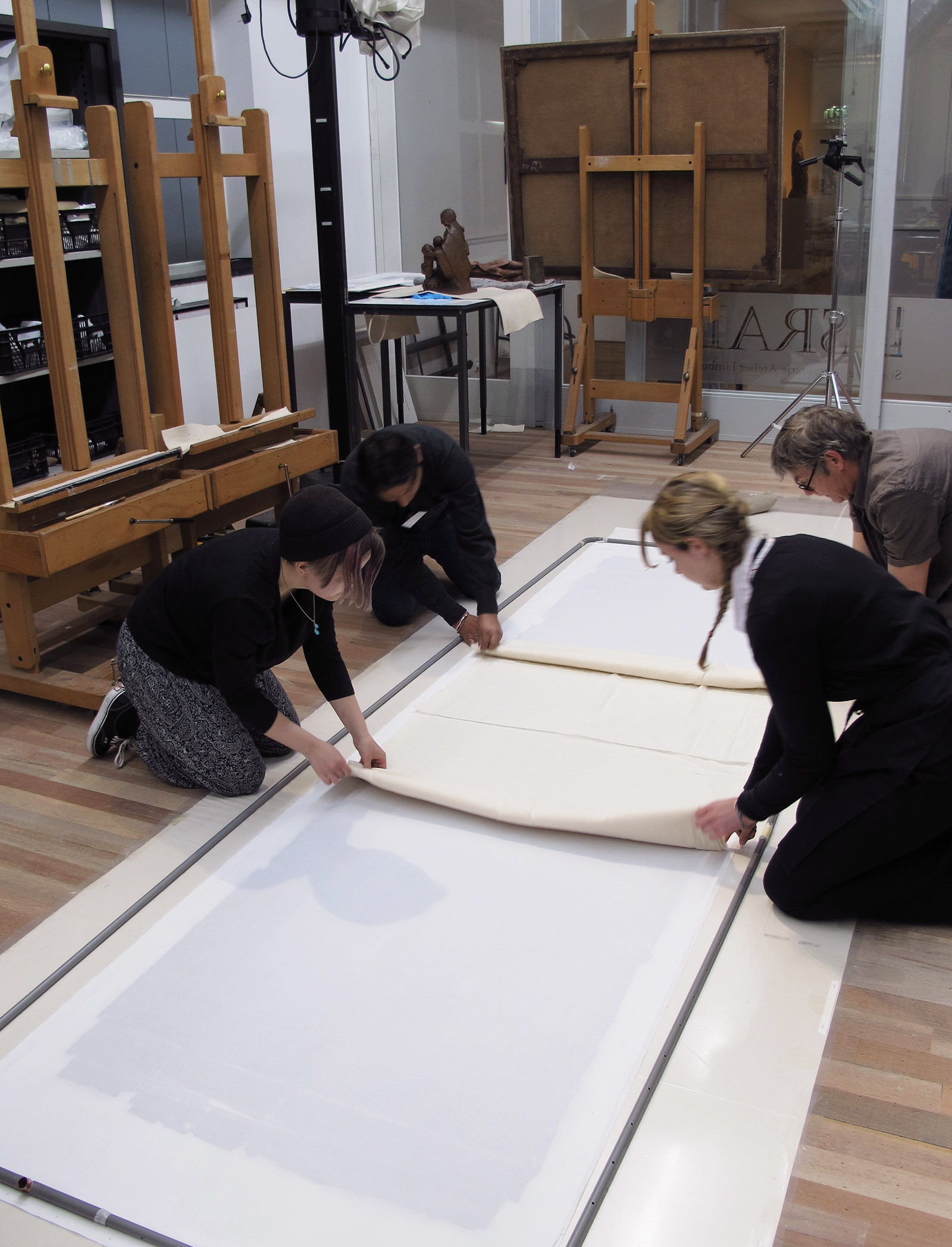 Four conservators sit on the floor and prepare a canvas lining.
