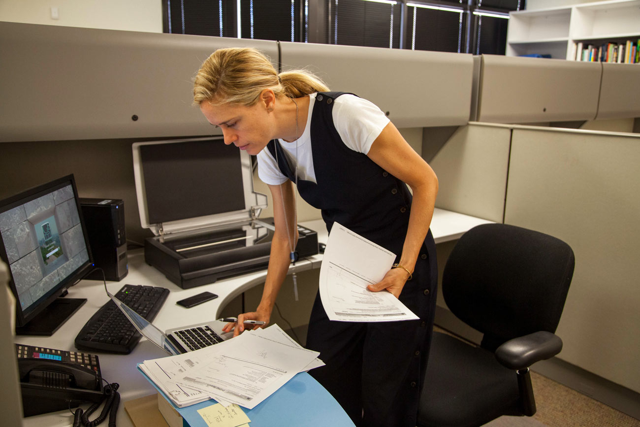 The same woman stands at a desk next to a scanner holding documents in one hand and typing on a laptop computer with the other