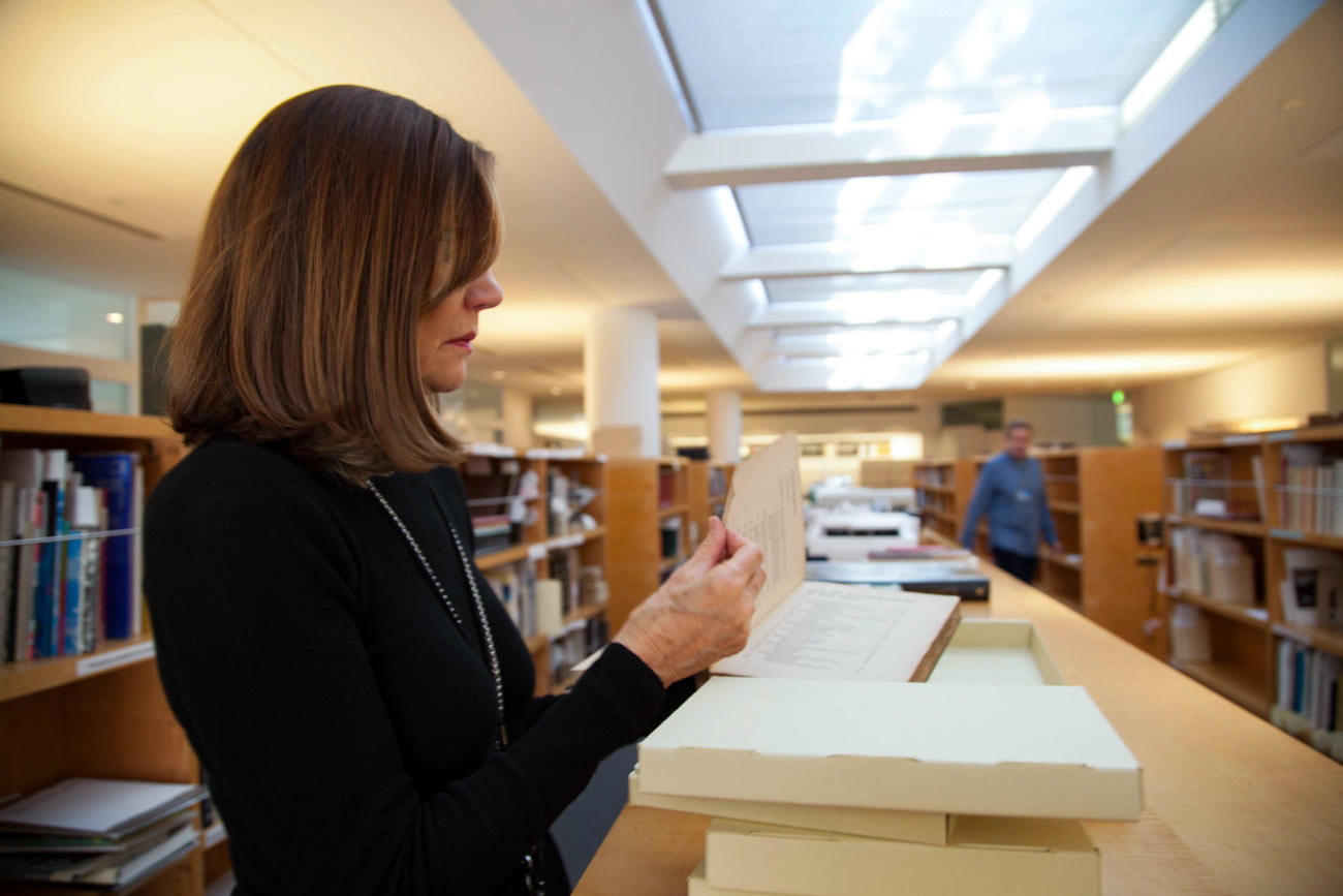 A woman stands in a library, working on top of a low book shelf, examining the page of a book surrounded by book-sized boxes