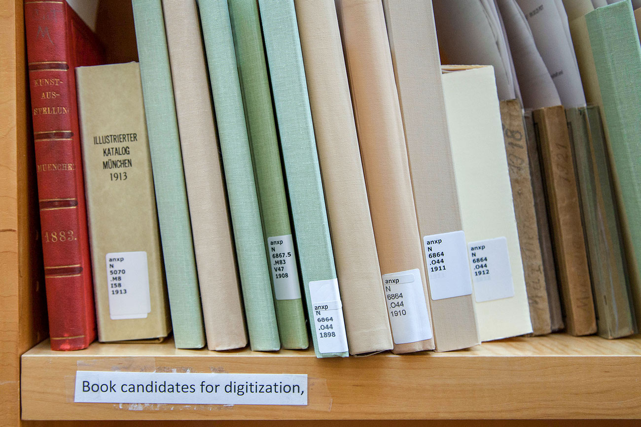 "Books on a shelf with library labels on the spine and a label taped to the shelf reading ""Book candidates for digitization"""