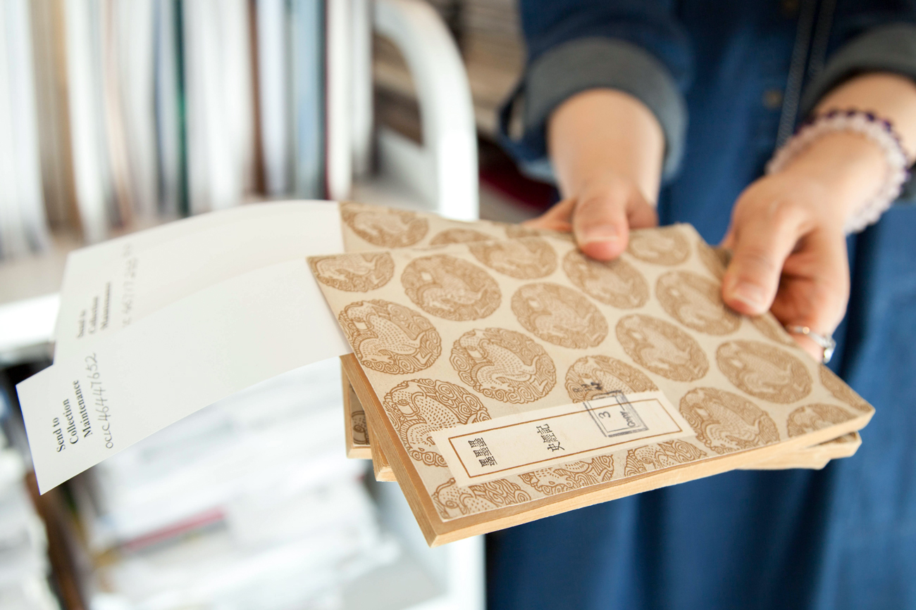 "A woman holds three books with Chinese lettering and repeating horse pattern on the cover. Pieces of paper hanging out of the books read ""Send to Collections Maintenance"""