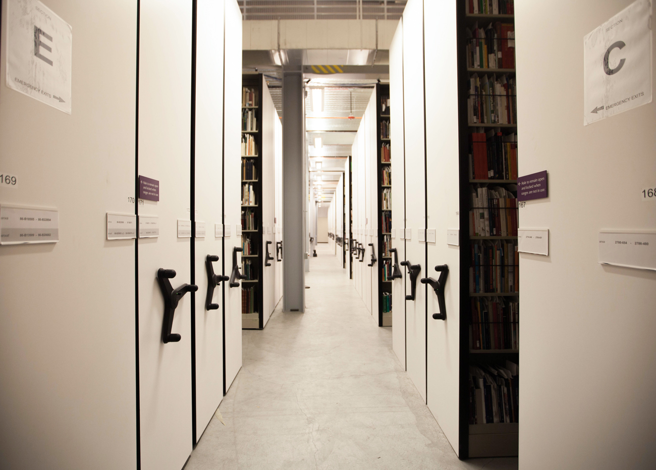 A view down the aisle of a bright modern library. Floor-to-ceiling book shelves have cranks to move them to save space and allow access to the books.