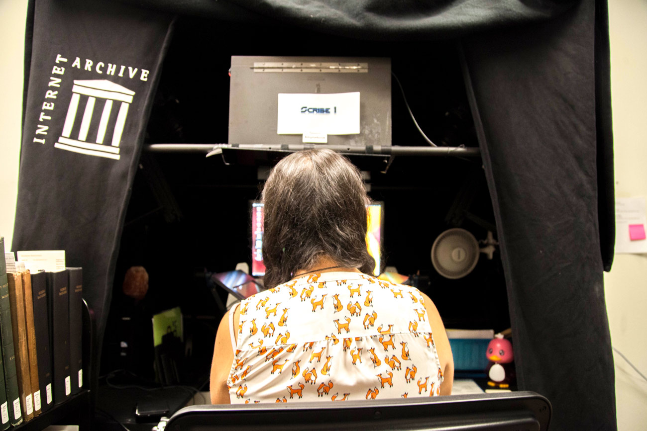 "A woman sits in front of a book scanner. The tent over the scanner reads ""Internet Archive."""