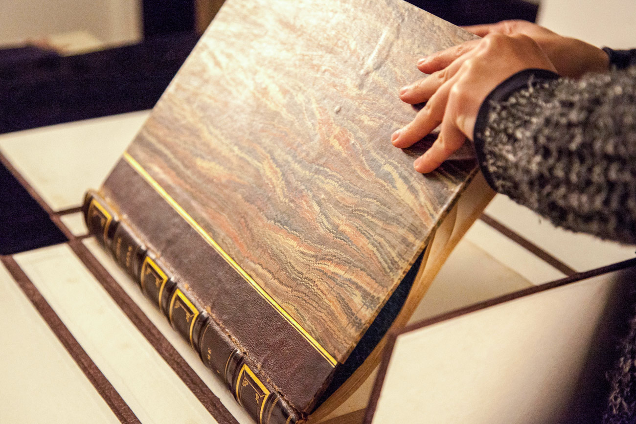 A technician opens an old-looking book with leather binding and gilt designs and lettering.