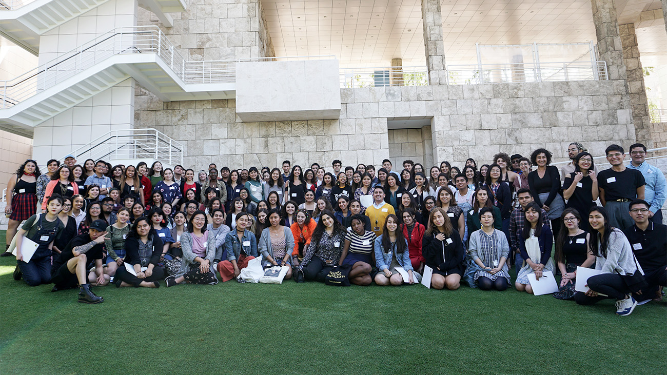 In front of the travertine-lined walls of the Getty Center, a large group of students of color sit and stand in an arc on grass.
