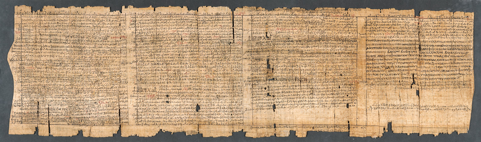 A flat papyrus scroll, yellowed with age and missing some pieces, with many lines of small hand-painted letters
