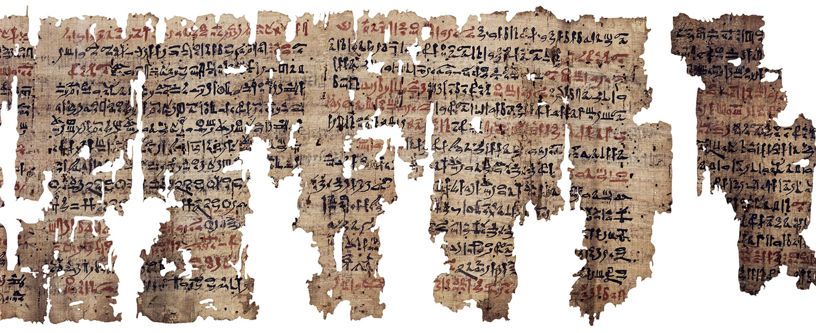 A flat papyrus scroll with ragged edges and many missing pieces, inked densely with letters in hieratic