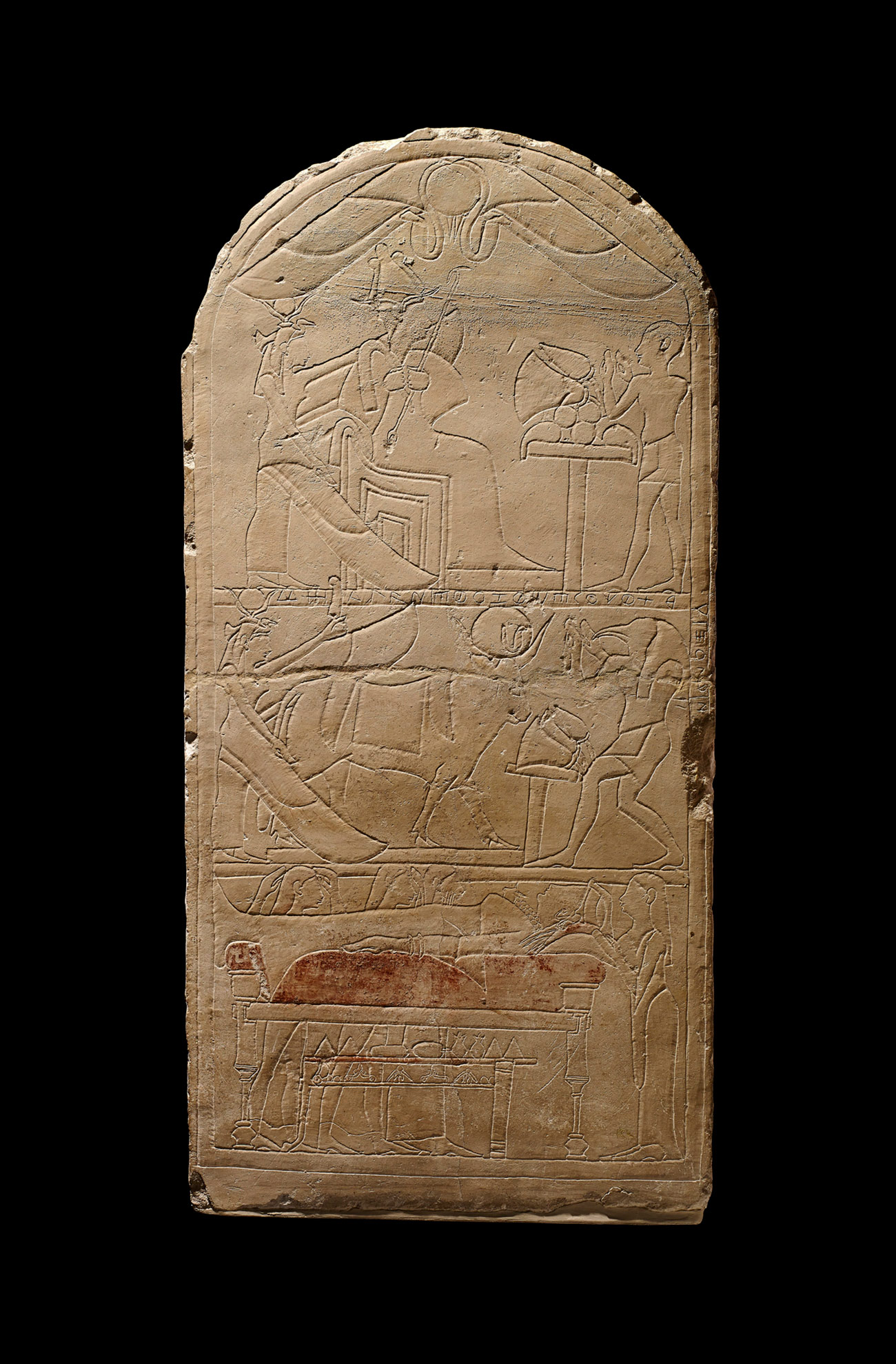 An inscribed limestone block, in the shape of a gravestone, depicts the deceased and Egyptian dieties with elegantly incised lines