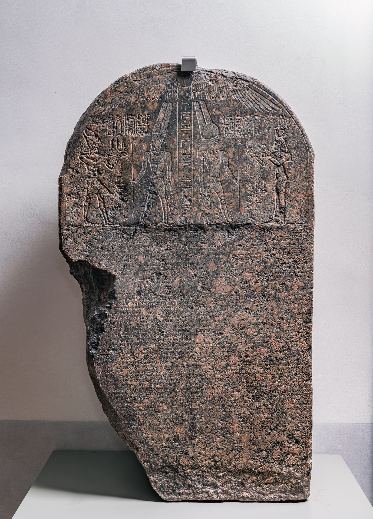 A large, upright, chipped slab of dark, purplish granite incised with multiple lines of ancient Egyptian text