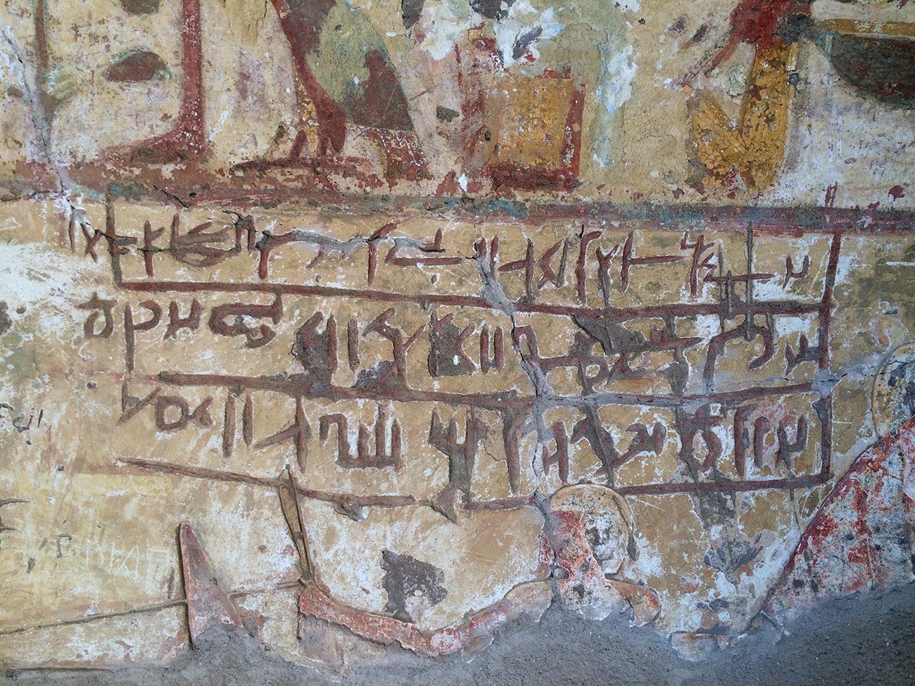 Close-up of three rows of inscribed Demotic letters on a yellow-tinted, painted Egyptian frieze inside a tomb