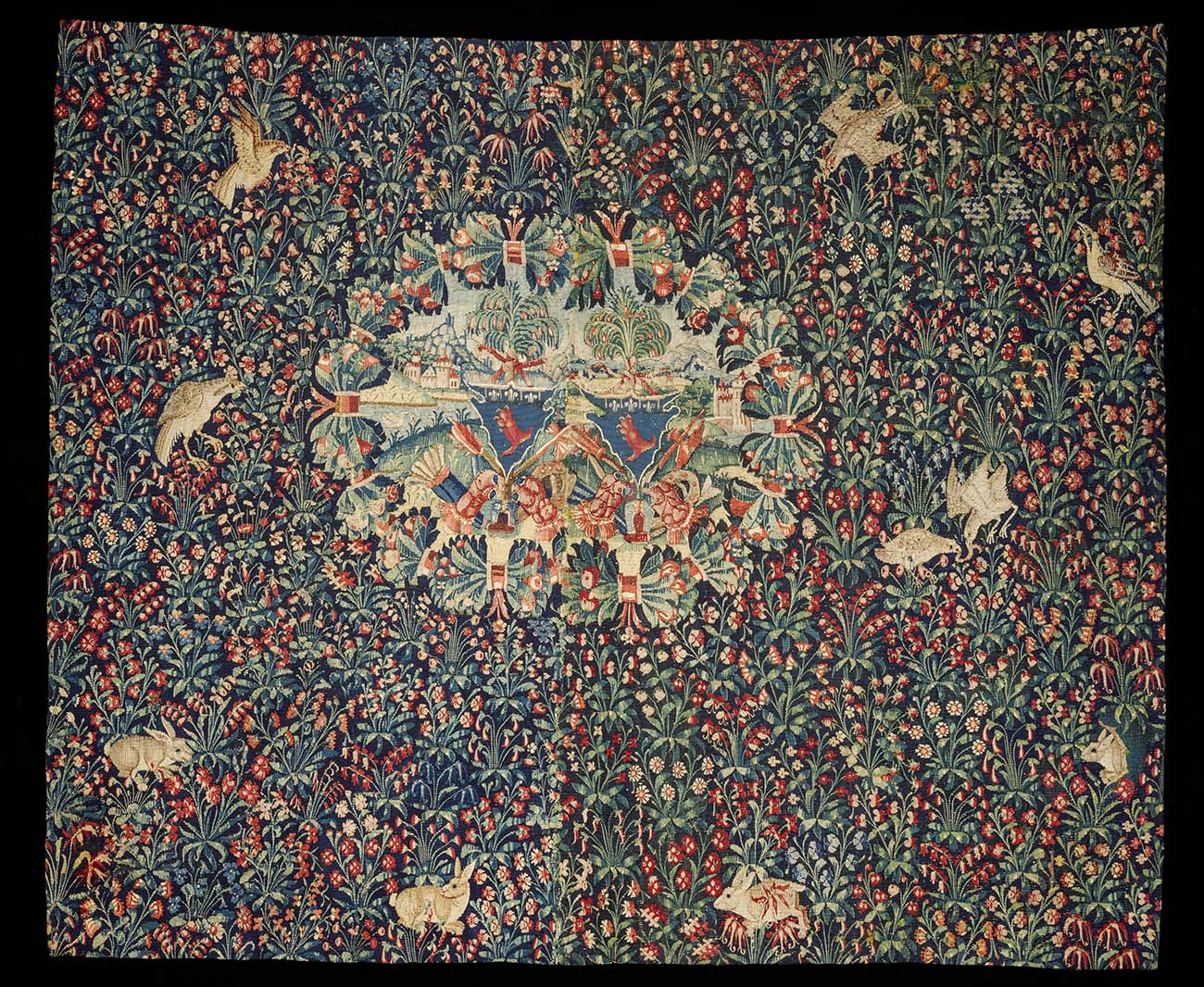 Colorful tapestry featuring birds, rabbits, and flowers.