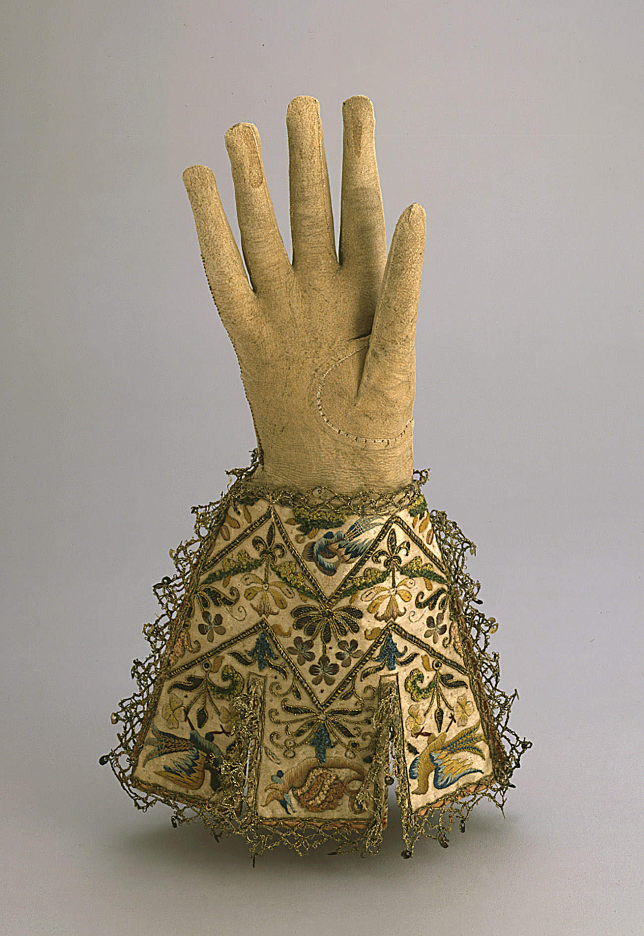 Mustard color glove with embroidery around the wrist.