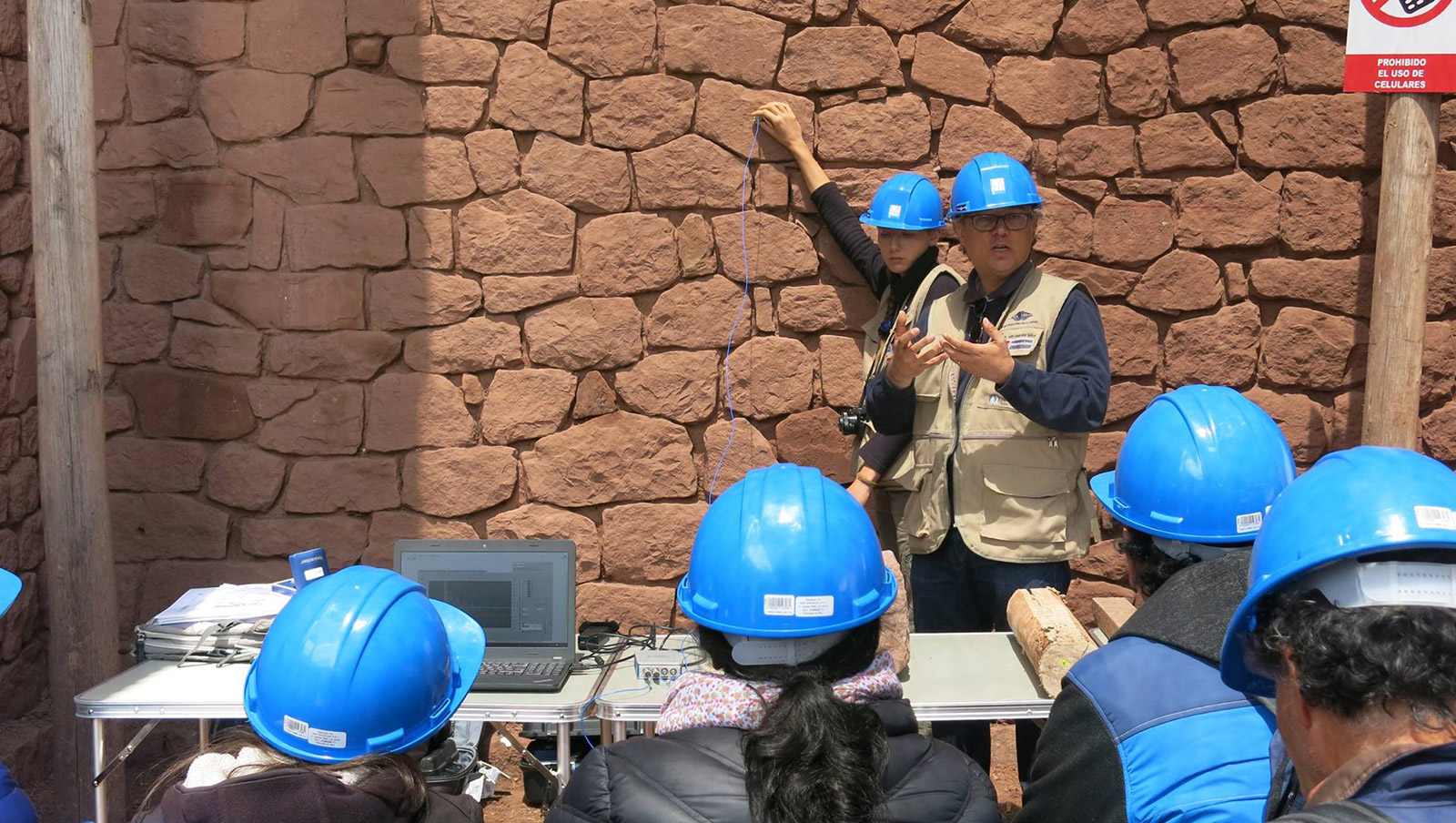 Several people in blue hard hats look on as a brick wall of an earthen building is tested and explained, to ensure that it can withstand earthquakes