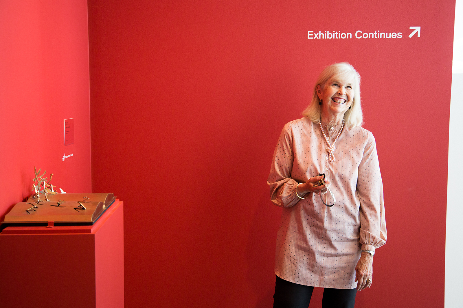 A blonde woman wearing a pink tunic smiles standing in front of a red wall