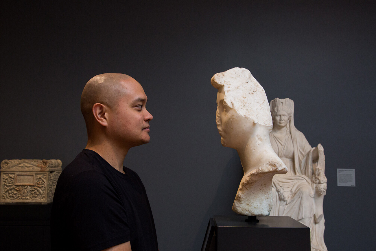 A man stands face to face with an ancient roman bust of a woman.
