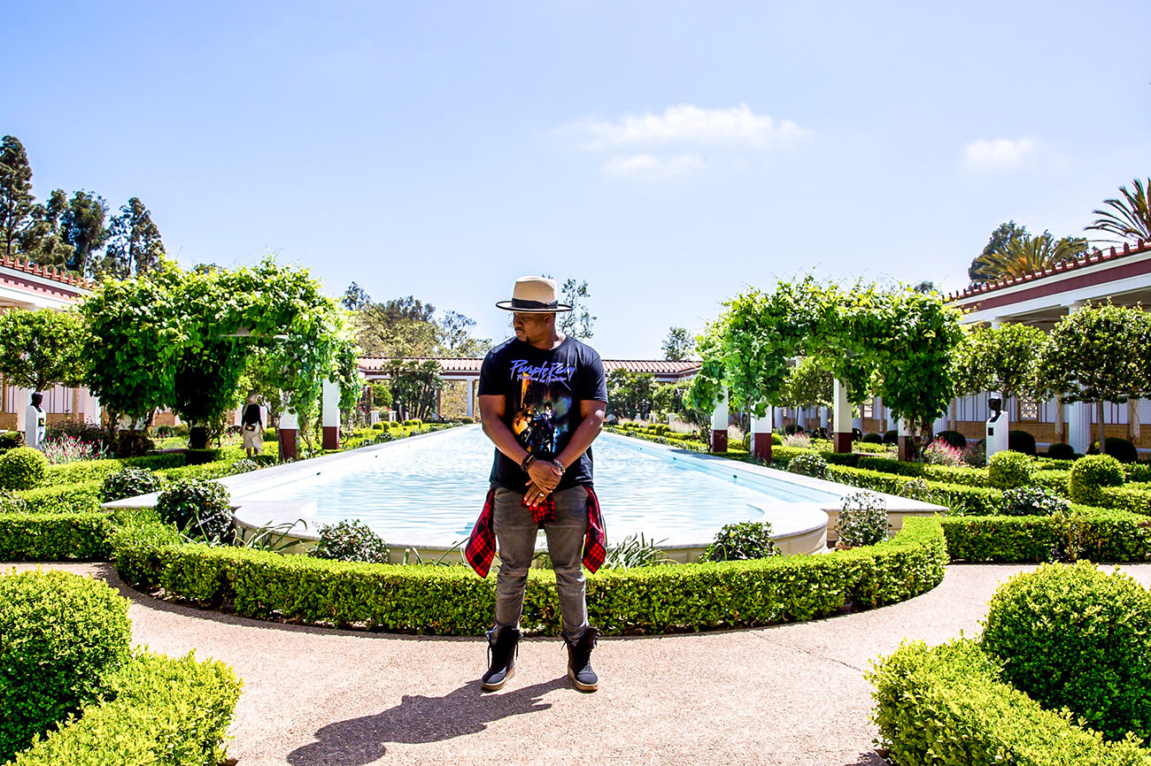 DJ M.O.S. stands in the center of a lush green garden with a shallow pool at the center.