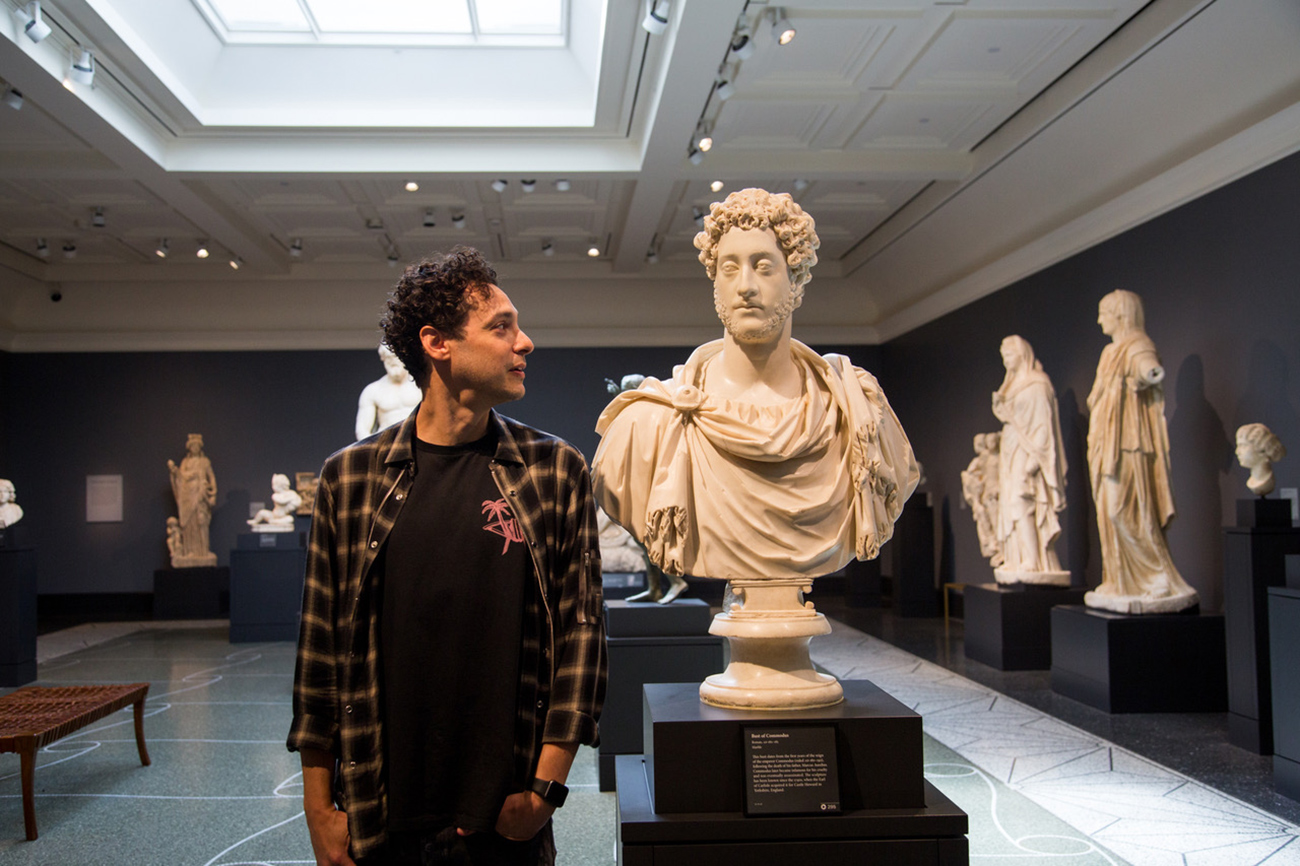 DJ Spider stands next to a Roman bust in the galleries of the Getty Villa.