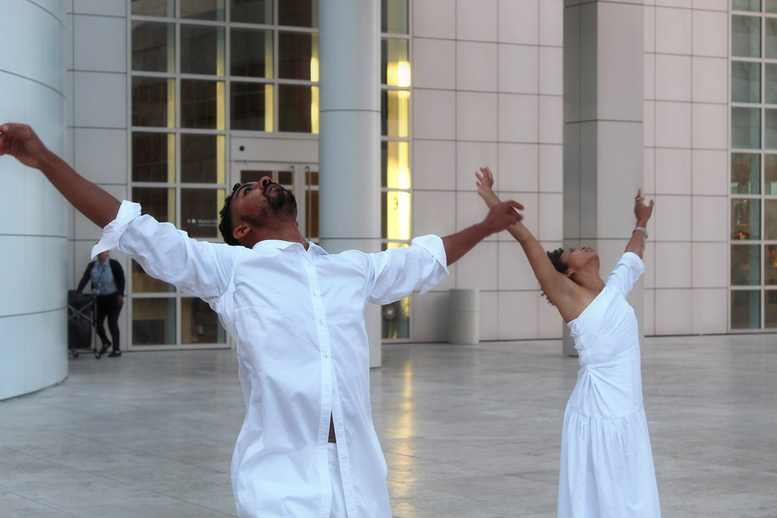 Two Black dancers in white garb reach their arms to the sky, heads thrown back