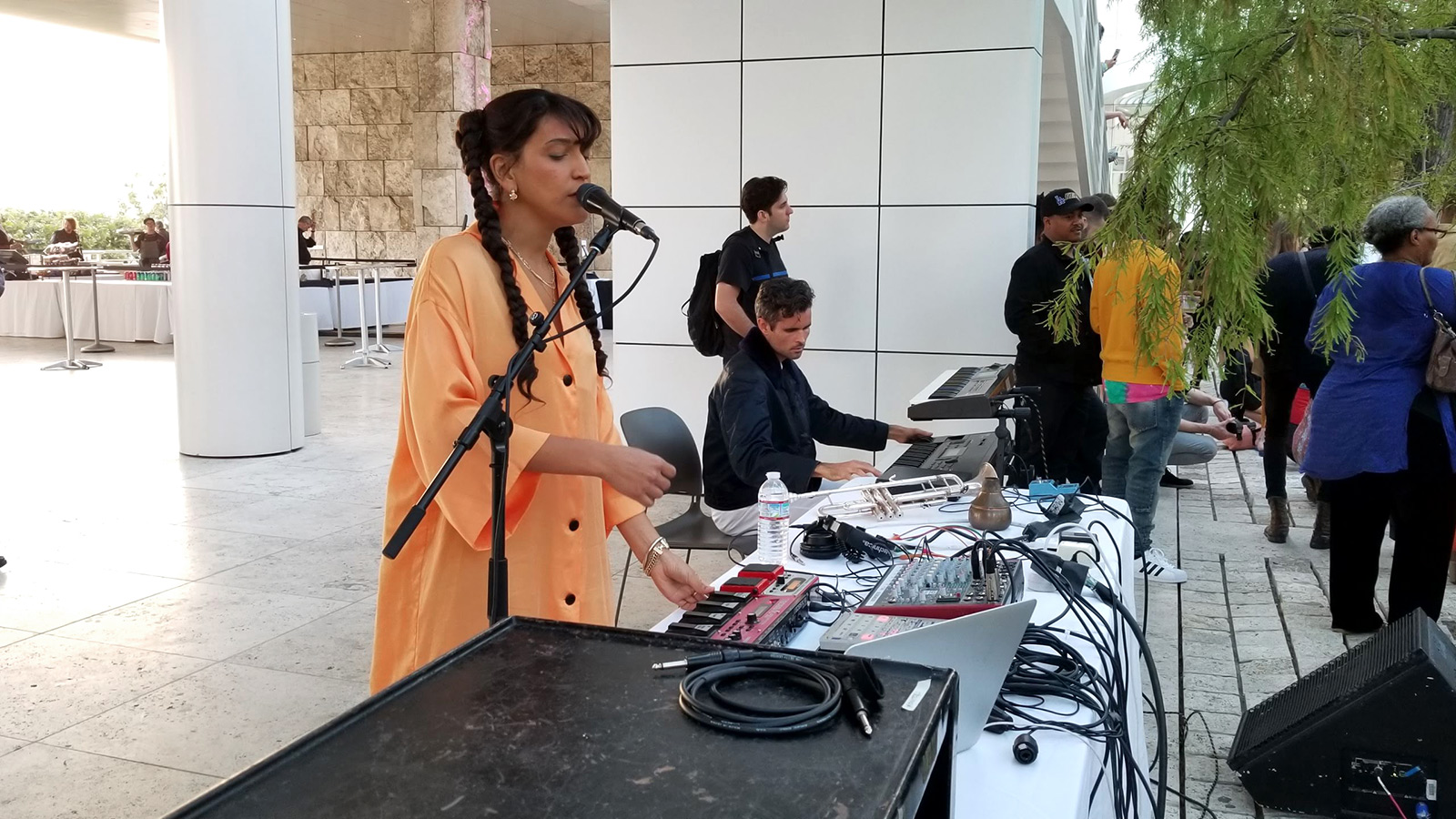 A woman with long braids and flowing orange robes stands at a DJ booth, speaking into a microphone on a stand