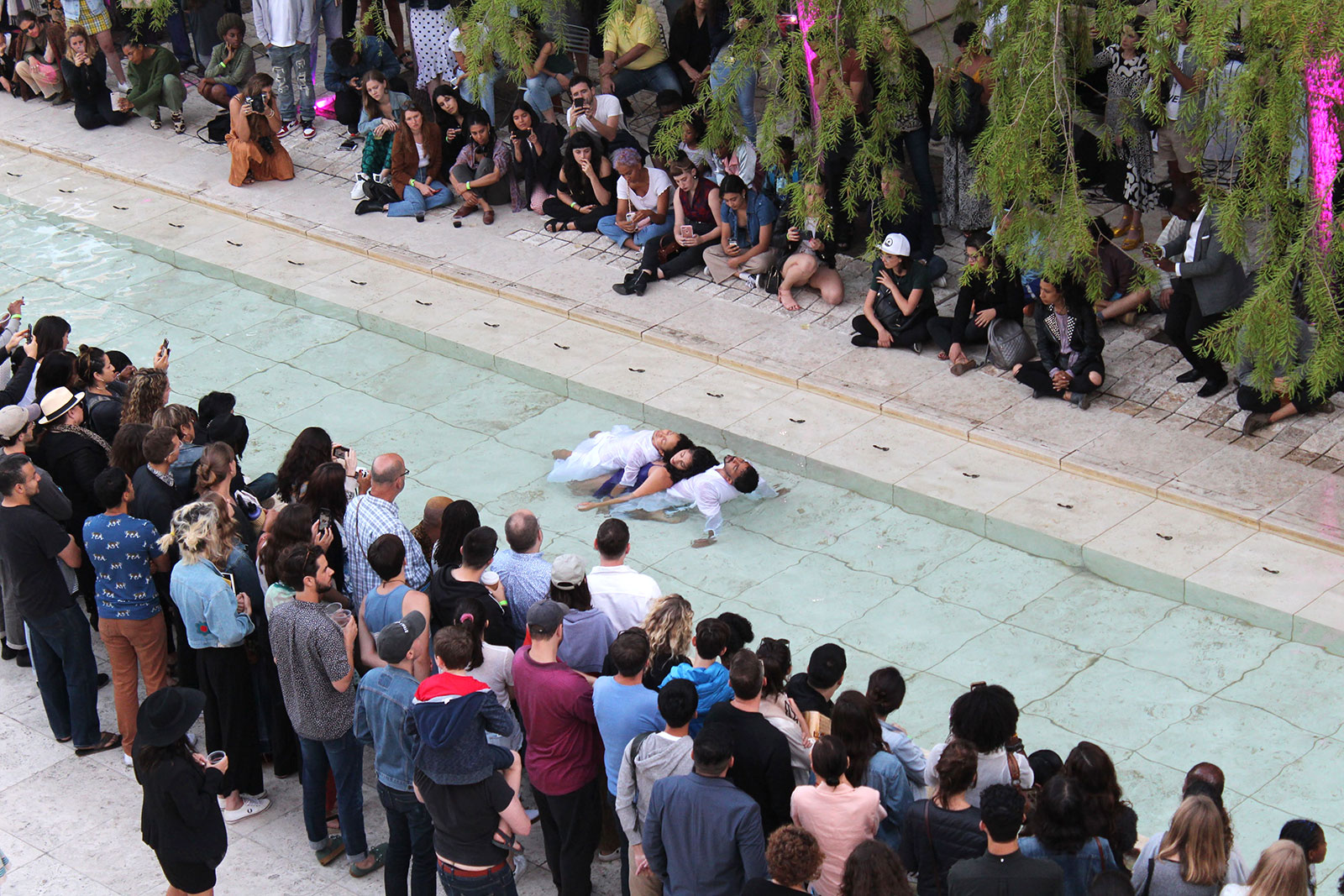 Overhead view of three dancers lying together, bodies touching, in a shallow reflecting pool