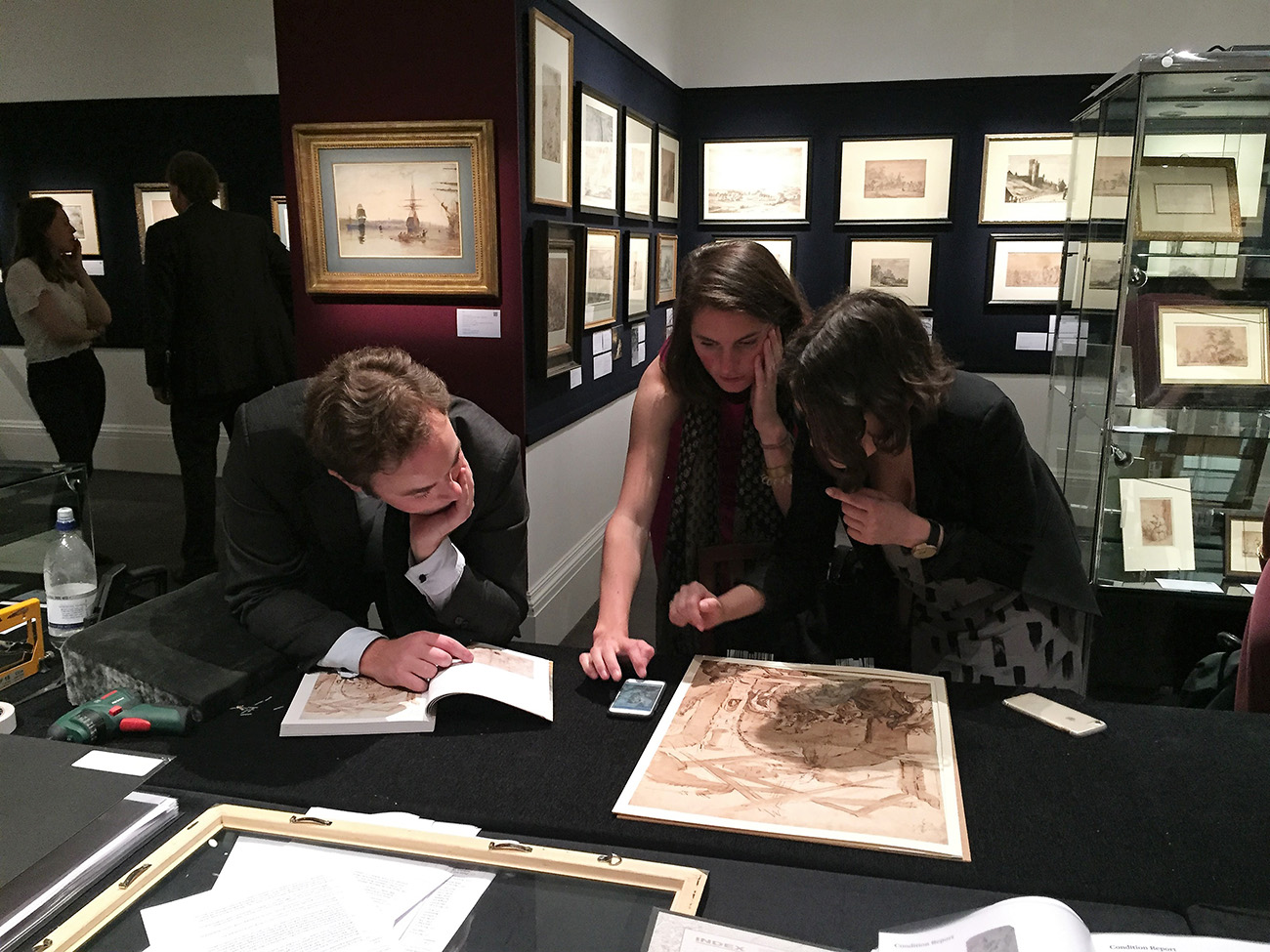 Two seminar participants take a closer look at a drawing outside of its frame with Alexander Faber, during the Old Master Drawings sale preview at Sotheby's London.