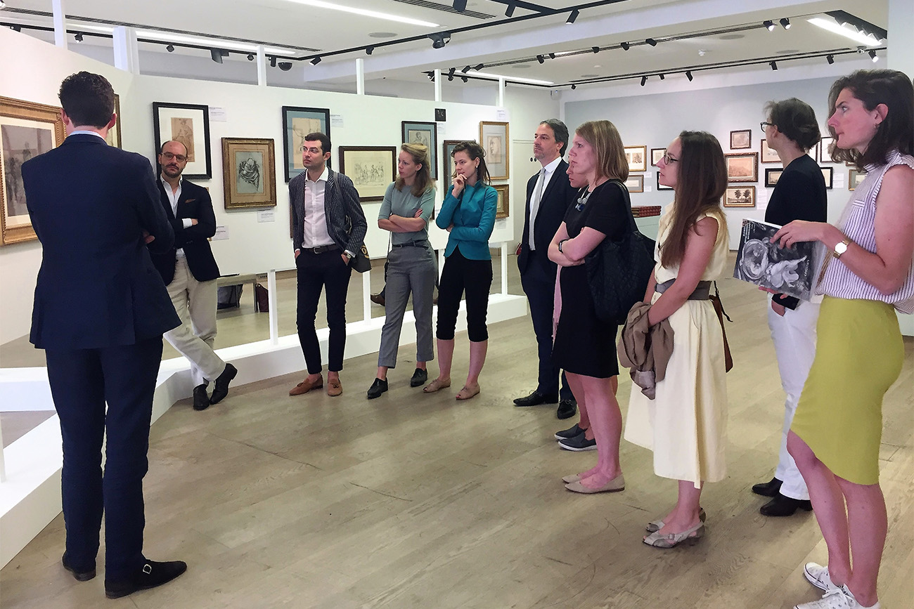 A group of participants stand in a show room of Old Master drawings.