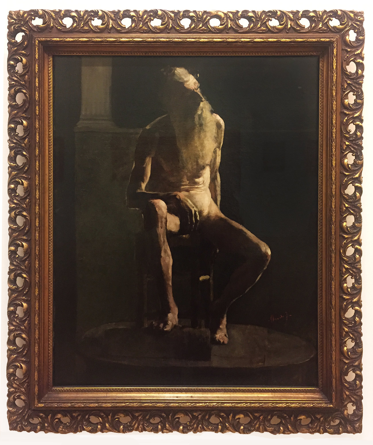 In a gilded frame, a dark painting of an anguished looking, emaciated man seated on a chair and looking up to his left, to the source of a dim light