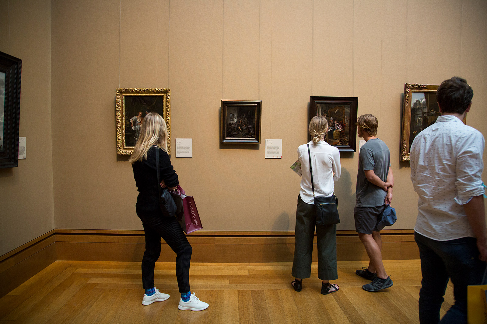 Four people in a museum gallery look at small, darkly colored paintings by Dutch artists arrayed on a wall