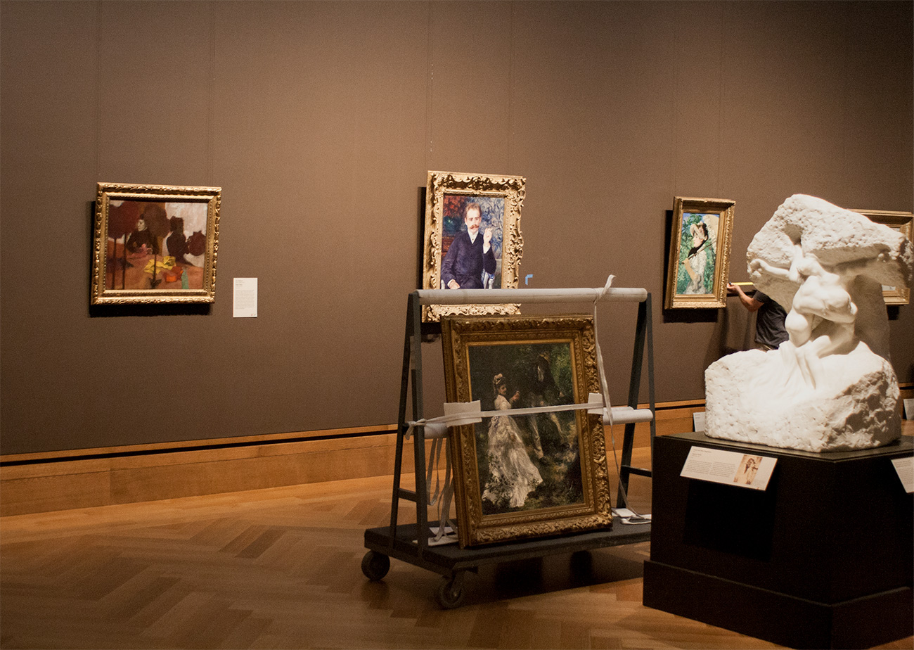 In a gallery of French art with brown walls, a painting by Renoir sits strapped to a cart in preparation for travel