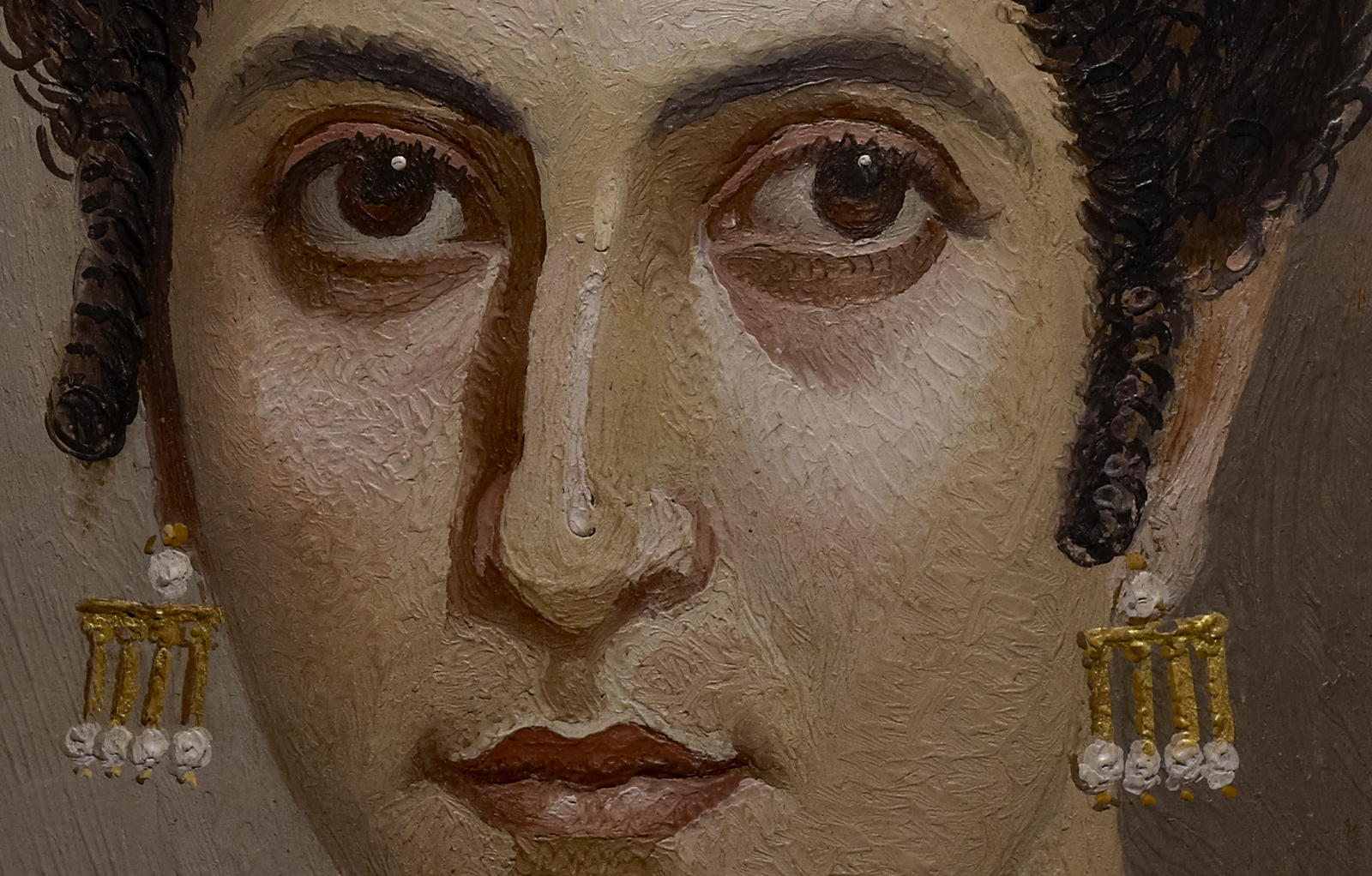 A close up of a mummy portrait featuring a woman with gold jewelry.