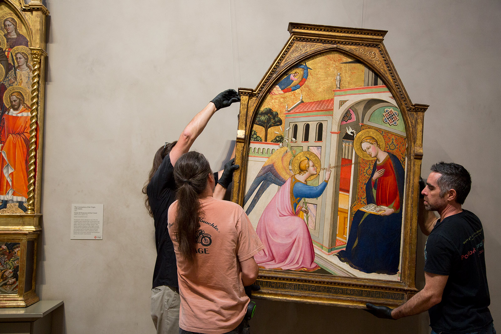 Three preparators carefully install a panel painting by Tommaso del Mazza.