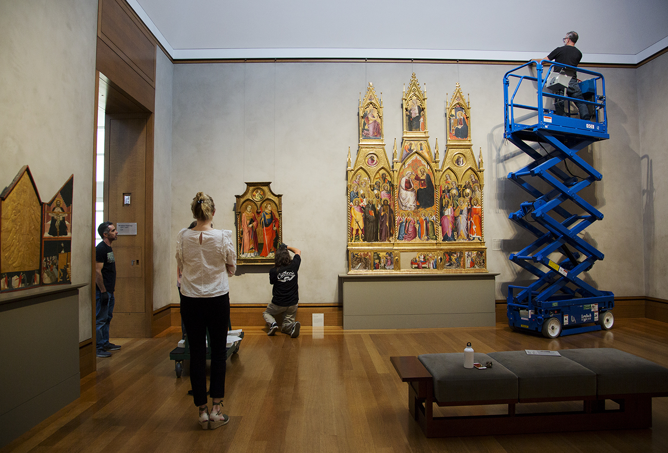 A wide view of a gallery featuring Renaissance era panel paintings. A preparator rides a lift to hang wires in one corner while another preparator measures the height of a painting on the wall.